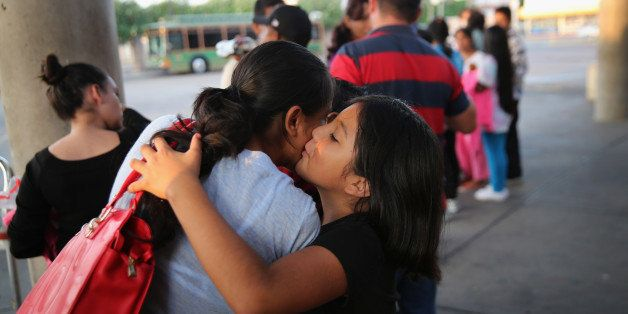 MCALLEN, TX - JULY 25:  Immigrants embrace at the Greyhound bus station before departing to various U.S. destinations on July
