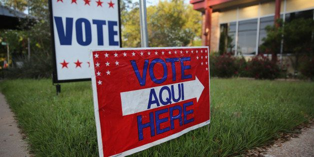 AUSTIN, TX - APRIL 28:  A bilingual sign stands outside a polling center at public library ahead of local elections on April