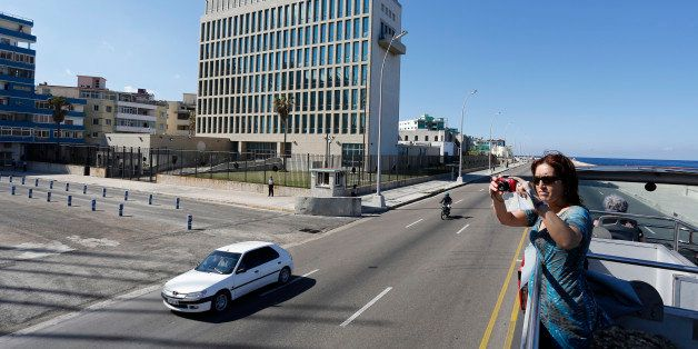 In this Dec. 18, 2014 photo, a tourist takes pictures from a double decker sightseeing bus as she passes the U.S. Interests S