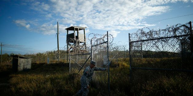 In this photo reviewed by the U.S. military, a soldier closes the gate at the now abandoned Camp X-Ray, which was used as the
