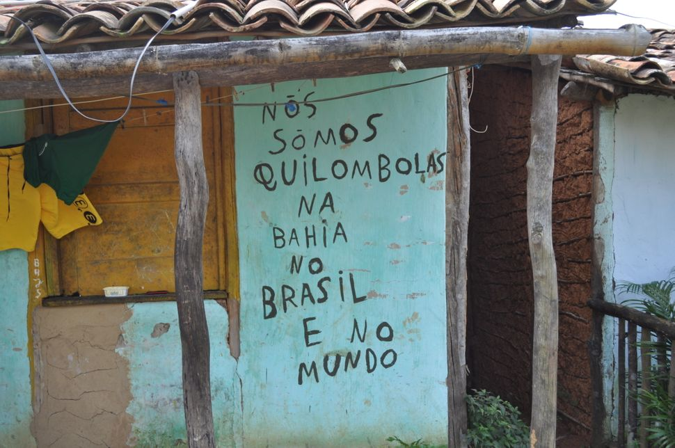 "A message scrawled on the wall of a house in São Francisco do Paraguaçú reads ""We're quilombolas in Bahia, in Brazil and in t"
