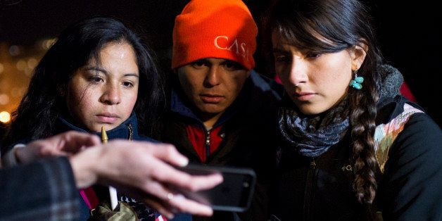 UNITED STATES - NOVEMBER 20: Immigration reform activists in front of the White House use a smartphone to watch President Bar