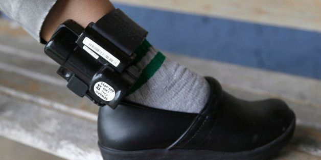 In this Monday, Sept. 23, 2013 photo, Belky Rubio shows her ankle monitor in Homestead, Fla. Rubio, who is an undocumented im