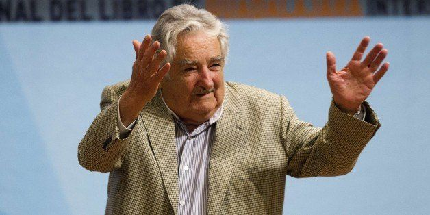 Uruguayan President Jose Mujica waves after participating in a conference on the last day of the International Book Fair in G