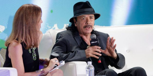 Musician Carlos Santana, right, gestures as he speaks during a question and answer session with interviewer Leila Cobo, left,