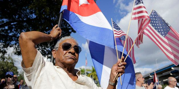 Evilio Ordonez holds Cuban and American flags during a protest against President Barack Obama's plan to normalize relations w