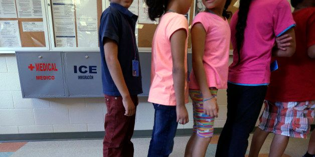 FILE - In this Sept. 10, 2014 file photo, detained immigrant children line up in the cafeteria at the  Karnes County Resident