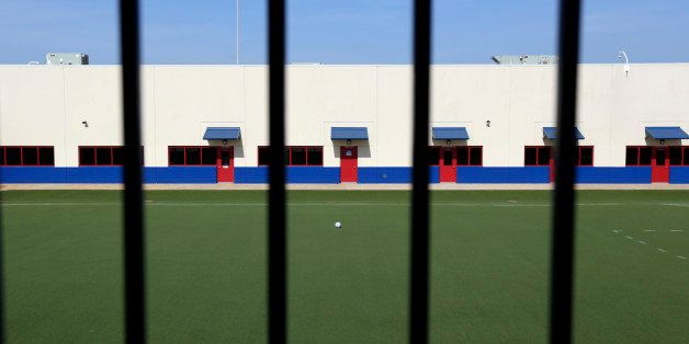 An artificial turf soccer field sits in the middle of the Karnes County Residential Center, Thursday, July 31, 2014, in Karne