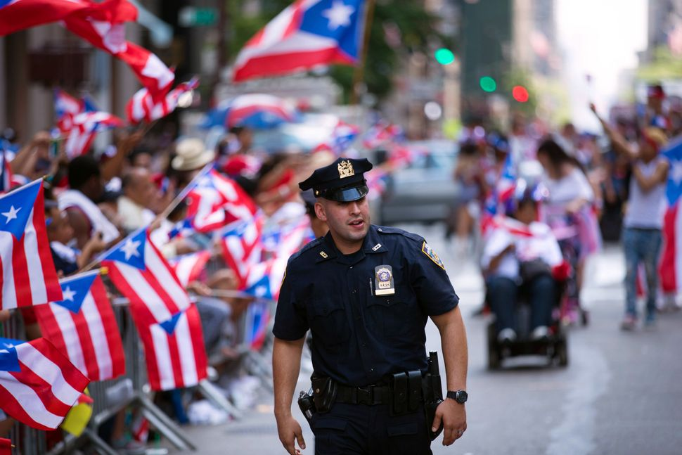 A police officers patrols during the annual Puerto Rican Day Parade as it makes its way up New York's Fifth Avenue, Sunday,