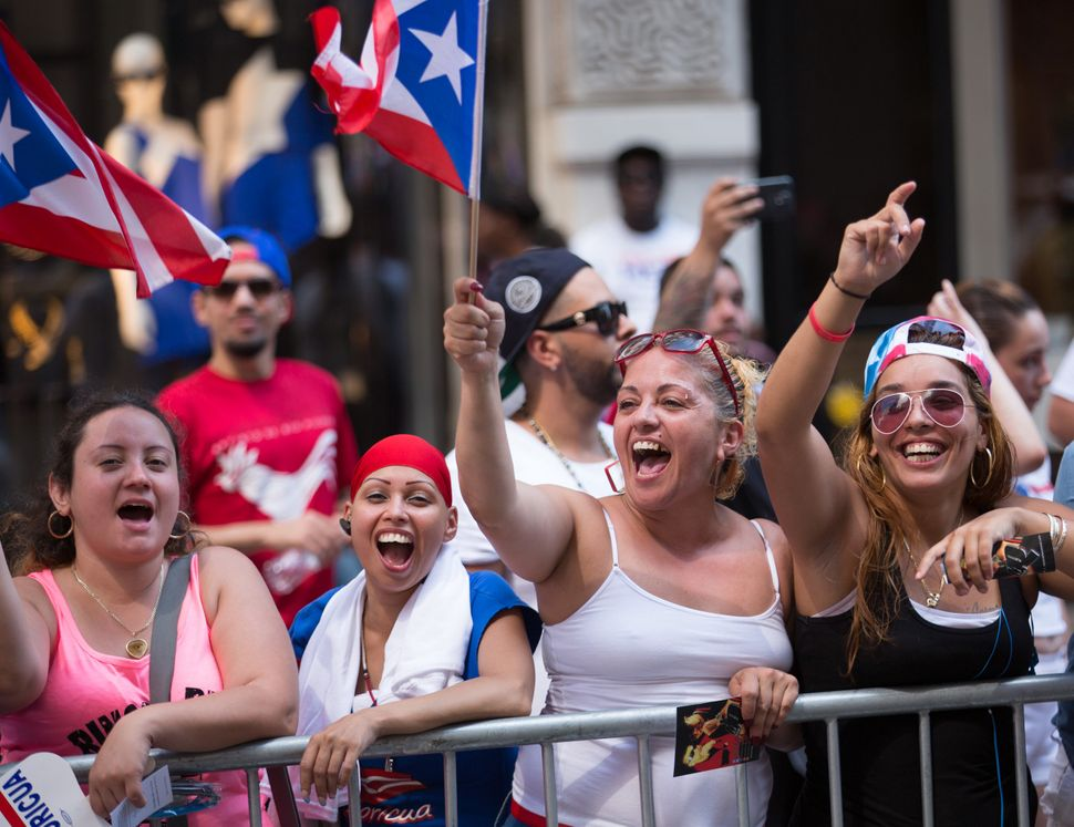 Spectators wave flags during the annual Puerto Rican Day Parade as it makes its way up New York's Fifth Avenue, Sunday,  June