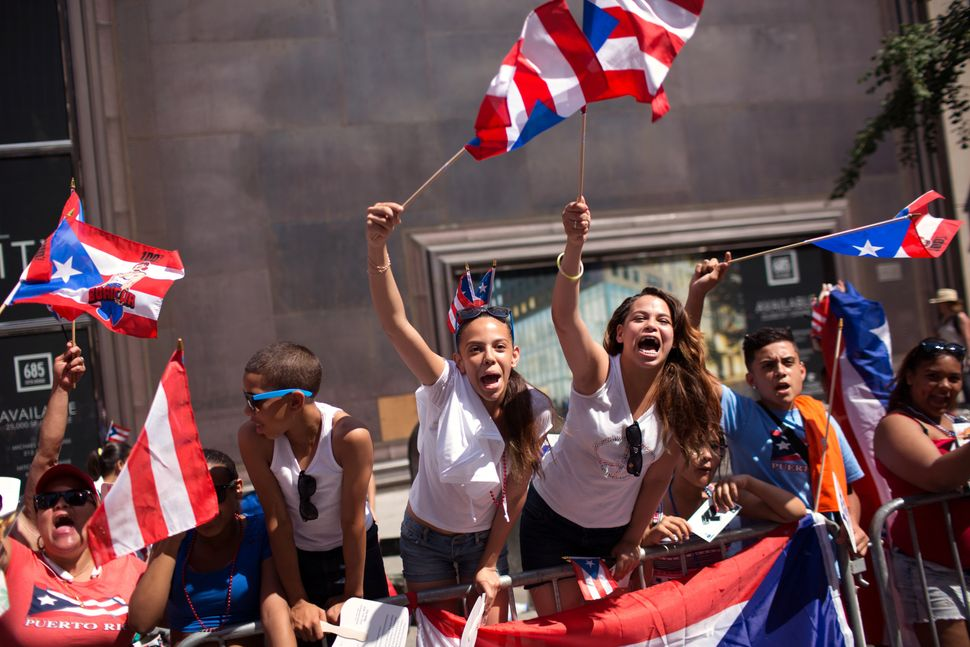 Spectators wave flags and cheer during the the annual National Puerto Rican Day Parade as it makes its way up New York's Fift