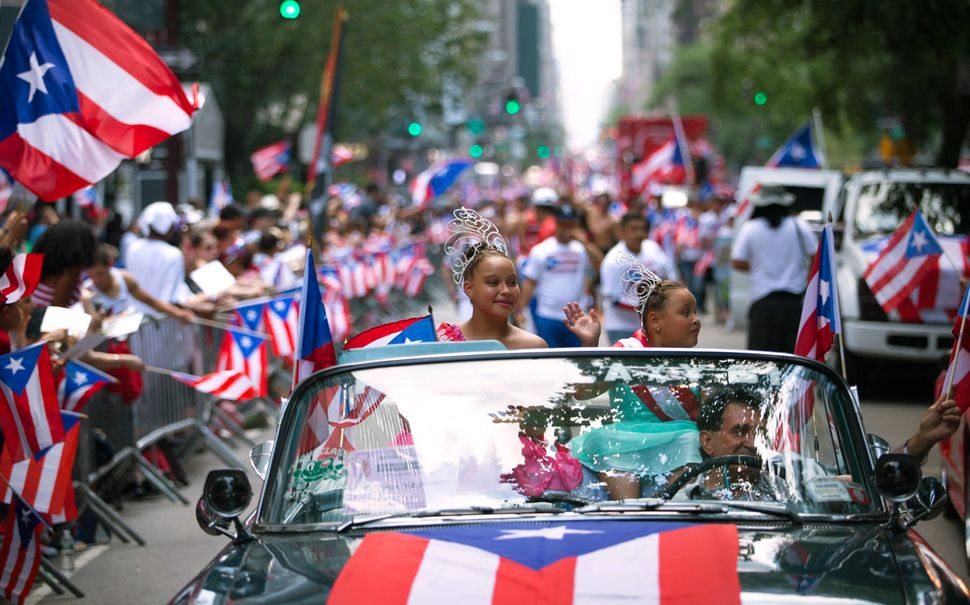 Jayda Vazquez, 12, left, and Kaylee Vazquez, 8, wave from atop a convertible in the procession as the annual National Puerto