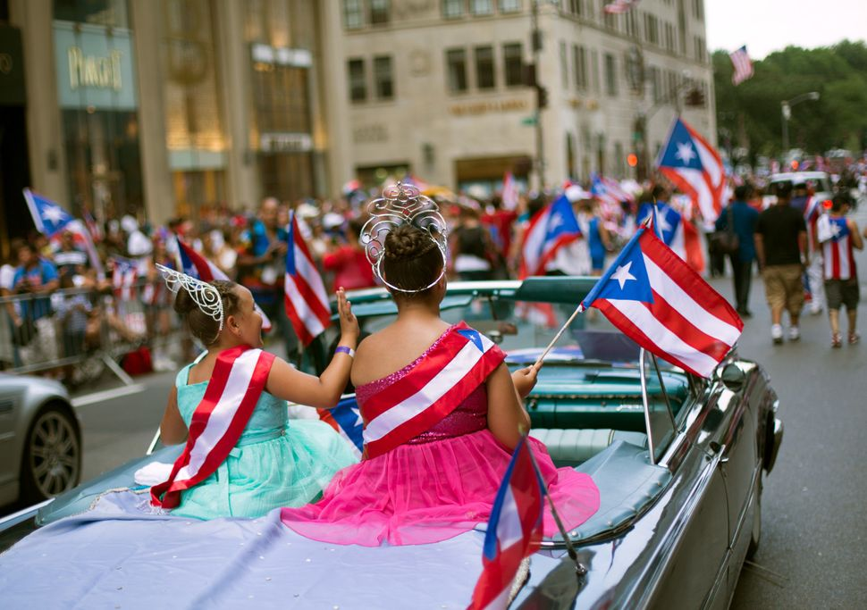 Kaylee Vazquez, 8, left, and Jayda Vazquez, 12, ride atop a convertible as the annual Puerto Rican Day Parade makes its way u