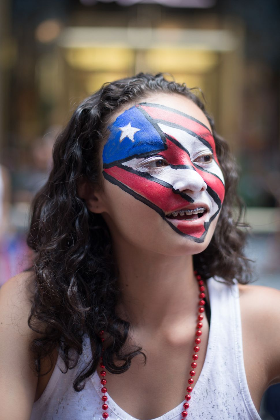 Nyasia Rodriguez, 14, watches as the annual National Puerto Rican Day Parade makes its way up New York's Fifth Ave., Sunday,