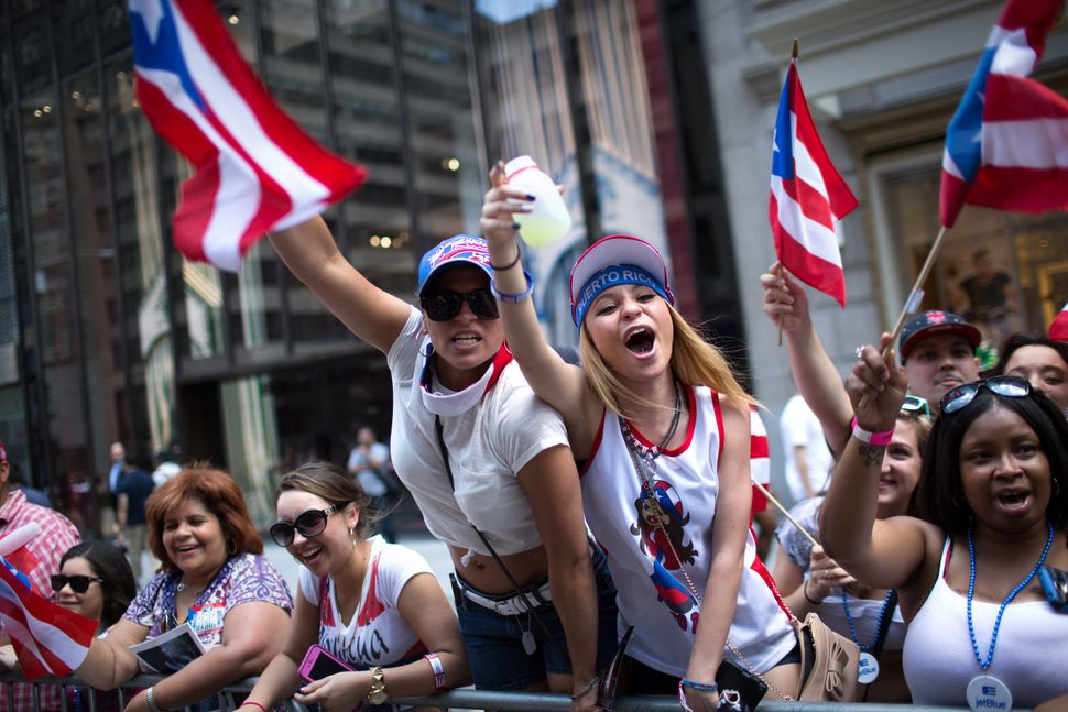 Arsenia Fuentes, center left, and Sarah Dones, center right, cheer for a passing float as the annual National Puerto Rican Da