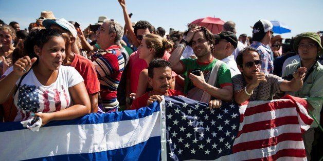 HAVANA, CUBA - AUGUST 14: A Cuban and American flag are trapped over the railing around a crowd of mostly Cubans with some Am