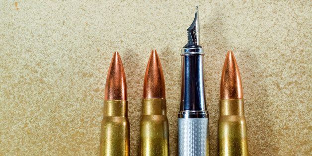 Pen and three bullets arranged verticaly on vintage background. Symbolize the confrontation between the power of the written