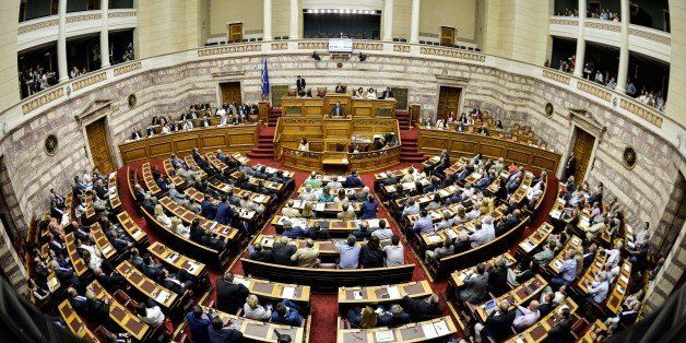 Greek Prime Minister Alexis Tsipras (rear C) delivers a speech during a parliamentary session at the Greek Parliament in Athe