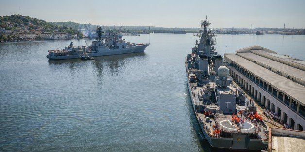 Cubans watch as the 'Moskva' Russian guide missile cruiser (R) and destroyer ' Vice Admiral Kulakov' (L) moor at Havana's har