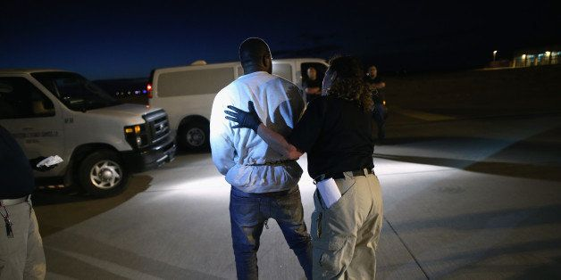 MESA, AZ - OCTOBER 15:  An undocumented immigrant is led towards an Immigration and Customs Enforcement (ICE), charter jet ea