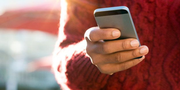 Close up of a young woman's hand typing text message on her smartphone. African young woman is typing on touch screen mobile