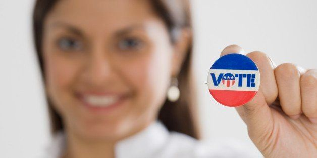 Indian woman holding up Vote pin