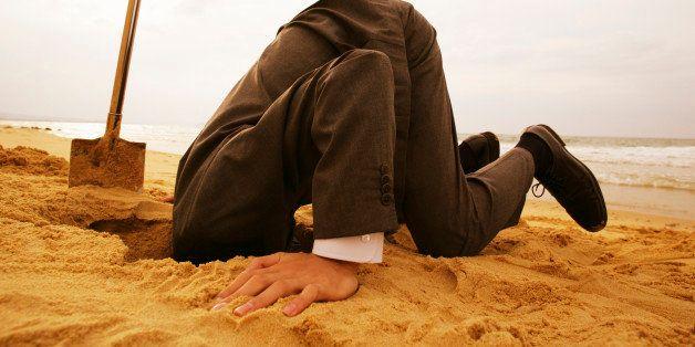 Businessman In Formal Wear Putting Head In Sand