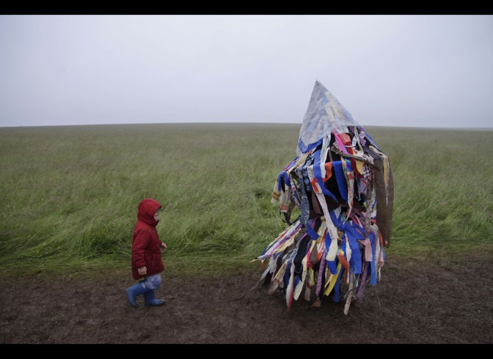 A man playing an accordion beneath a costume of torn fabrics and a child leave the Stonehenge monument in southern England. (