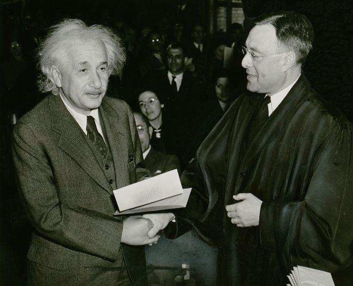 Photograph shows Albert Einstein receiving from Judge Phillip Forman his certificate of American citizenship.    Source Libra