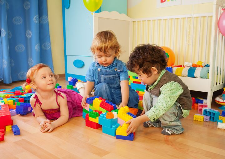 Kids playing with plastic blocks - two boys and girl