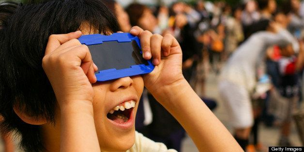 Boy looking at annular solar eclipse with eclipse glasses.