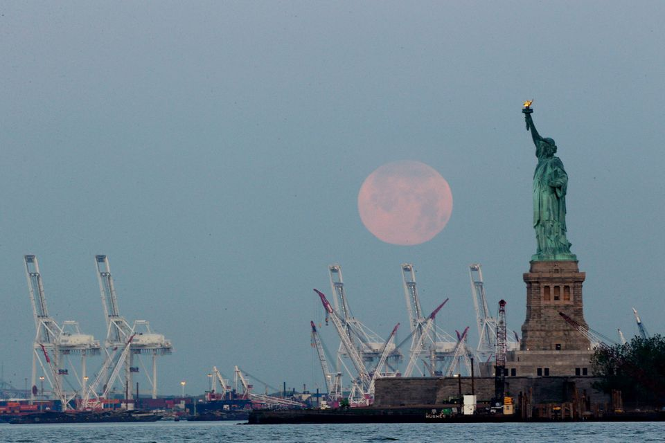 "A supermoon sets near the Statue of Liberty, Sunday, June 23, 2013, in New York. The larger than normal moon called the ""Supe"