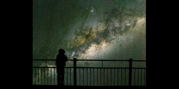 A child looks into space and the Milky way. Long exposure photograph from an astronomical observatory site.