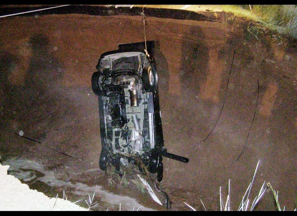 This image provided by the Utah Highway Patrol shows the wreckage of a car that ran into a hole, after heavy rain caused the