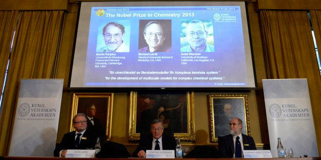 (L-R) Sven Lidin, Staffan Normark and Gunnar Karlstrom sit in front of a screen displaying the portraits of scientists (L-R)