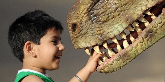 An Indian child plays with a park staff member wearing a dinosaur costume at the Adlabs Imagica theme park at Sangewadi some