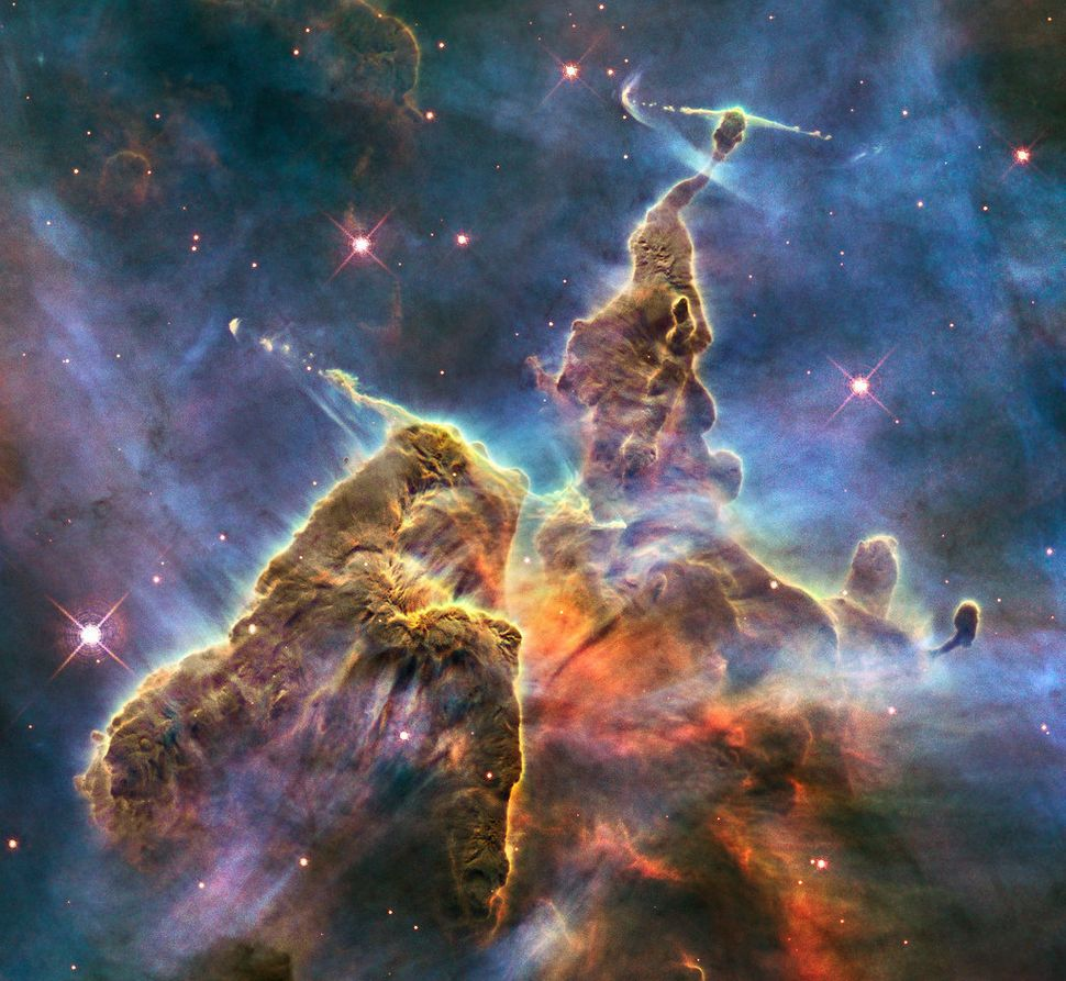This Hubble photo is of a small portion of a large star-birthing region in the Carina Nebula. Towers of cool hydrogen laced w