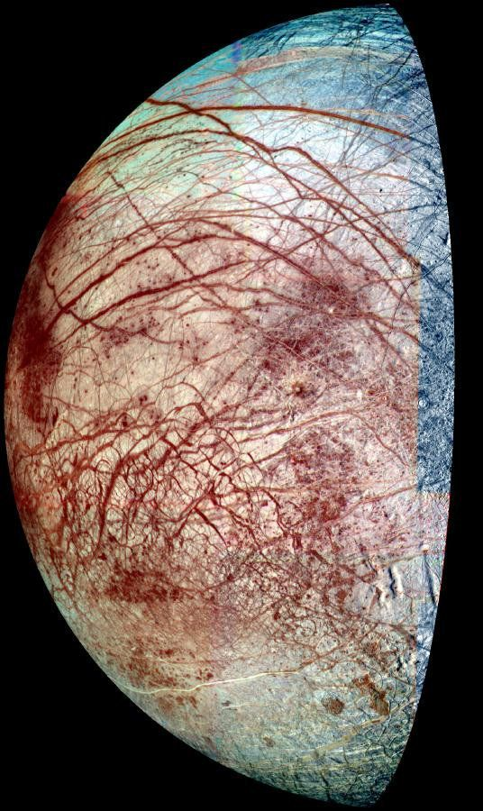 "The icy surface of Europa is shown strewn with cracks, ridges and ""chaotic terrain,"" where the surface has been disrupted and"