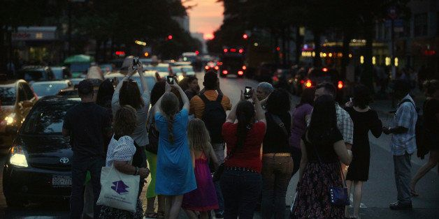 NEW YORK, NY - MAY 29:  People watch and photograph the sunset on 14th Street during 'Manhattanhenge' on May 29, 2013 in New