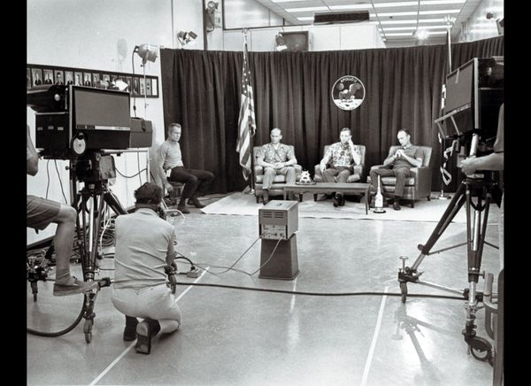 The space crew of the Apollo 11 mission sits in front of cameras answering journalists' questions during the night before the