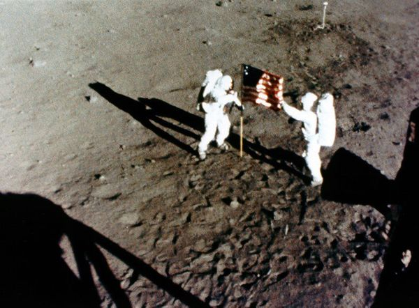 Armstrong and Aldrin raise the U.S. flag on the lunar surface.
