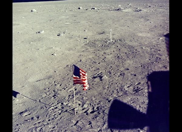 Flag and TV camera viewed from the lunar module window.