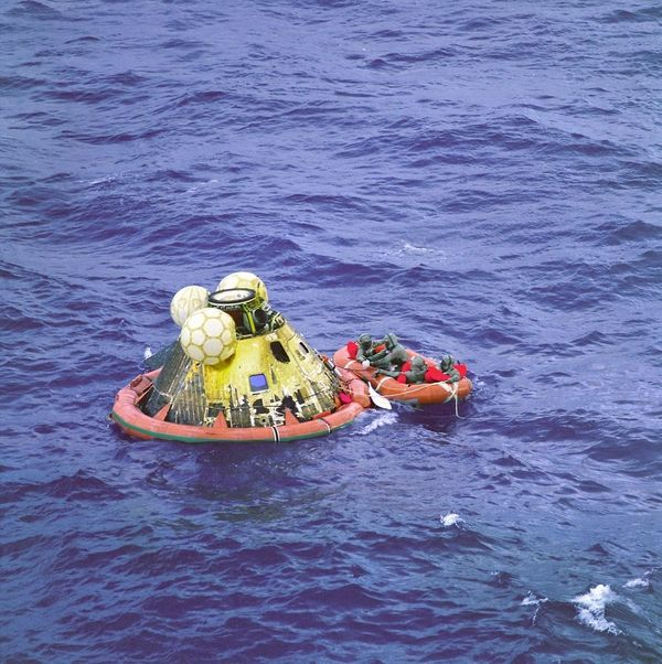 The Apollo 11 crew await pickup by a helicopter. The Apollo 11 Command Module Columbia splashed down at 11:49 a.m. CDT, July