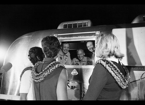 Apollo 11 astronauts, still in their quarantine van, are greeted by their wives upon arrival at Ellington Air Force Base on J