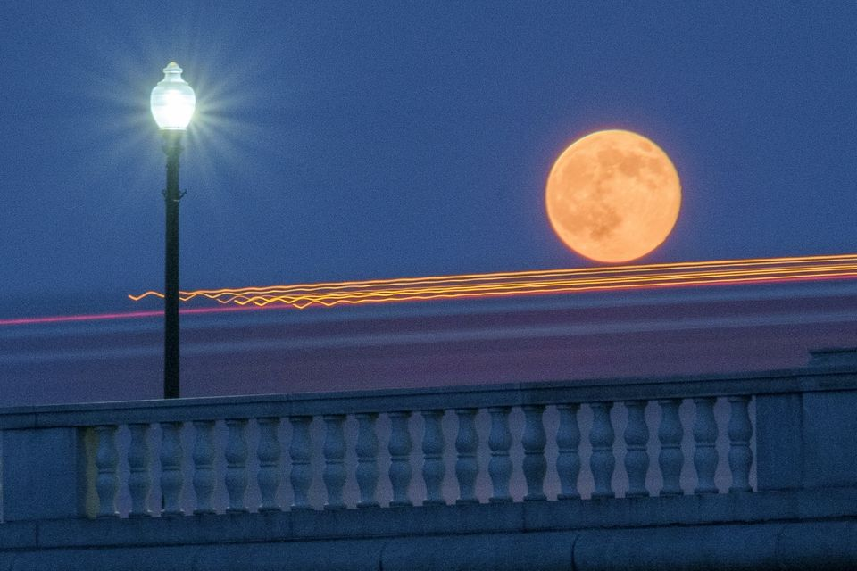 Traffic streaks by the supermoon as it rises behind the Memorial Bridge in Washington, Saturday, July 12, 2014. The full moon