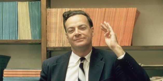 1959:  American physicist Richard Feynman (1918 - 1988) stands and raises one hand, in front of some shelves at Cal Tech Univ