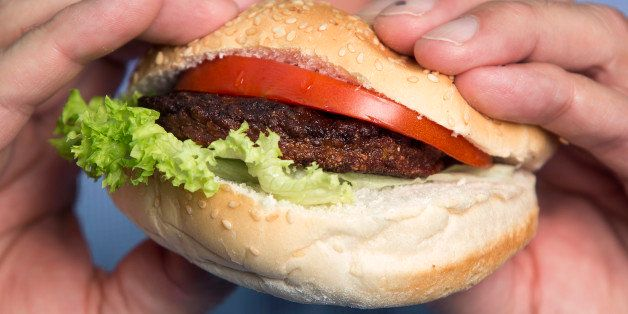 A beef burger created by stem cells harvested from a living cow is held for a photograph by Mark Post, a Dutch scientist, fol