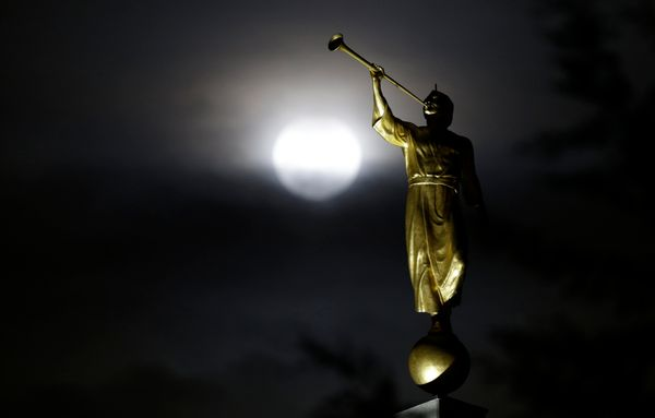 The earth's shadow begins to fall on the moon during the eclipse, behind the Angel Moroni statue in Bogota, Colombia.