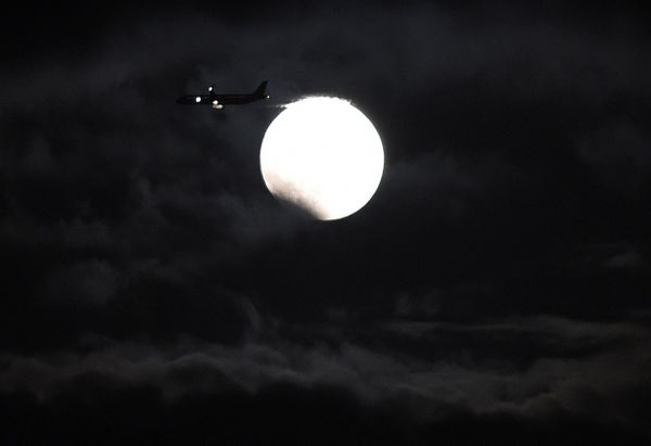 A plane flies before the moon during the eclipse in Yokkaichi, central Japan.