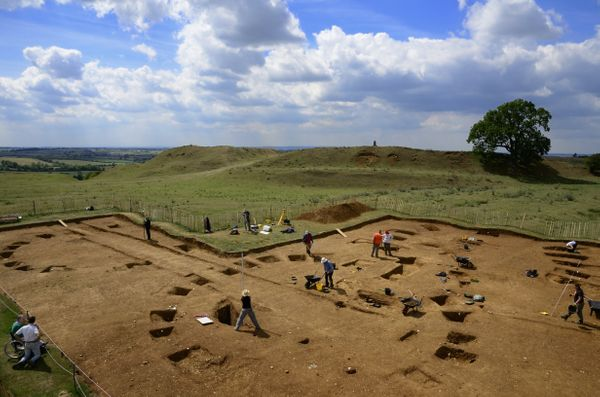 A more detailed view of Iron Age roundhouses under the excavation, and the hillfort in the background